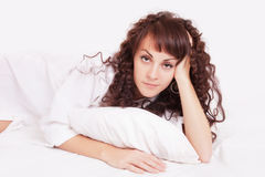 Beautiful woman in white shirt lying on a bed Stock Image