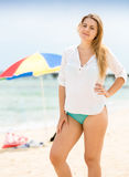 Beautiful woman in white shirt posing on beach against parasols Stock Photos