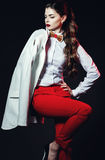 Beautiful woman in white shirt, wooden bow tie and red pants Stock Photo