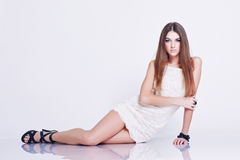 Beautiful woman in white short dress. Beautiful young woman in stylish short white dress posing on a floor in a studio Stock Image