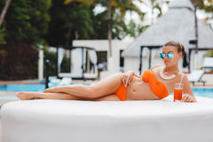 Beautiful woman on a white sofa near the pool Stock Photo