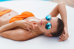 Beautiful woman on a white sofa near the pool Stock Image