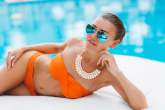 Beautiful woman on a white sofa near the pool Royalty Free Stock Photo
