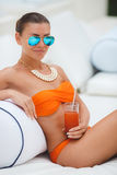Beautiful woman on a white sofa near the pool Royalty Free Stock Photos
