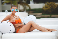 Beautiful woman on a white sofa near the pool. A beautiful woman,a brunette ,wearing sun glasses with blue mirror glasses,in an orange bikini on the neck is Stock Photos