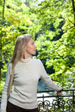 The beautiful woman in a white sweater on the bank of the lake.Portrait in a sunny day Royalty Free Stock Photo