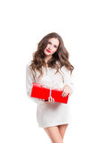 Beautiful woman in white sweater holding a red box with a gift. Royalty Free Stock Photos