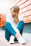 Beautiful woman in a white sweater, jeans and white sneakers sit. Ting on a tile near the orange wall Stock Images