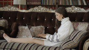 Beautiful woman in white sweater lying on elegant retro sofa with notebook stock video footage