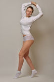 Beautiful woman in white sweater and panties dancing in studio Stock Image