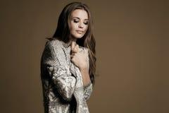 Beautiful woman in white sweater posing in studio Stock Photo