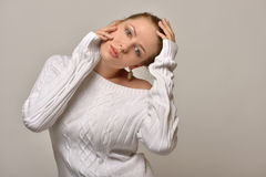 Beautiful woman in white sweater in studio Royalty Free Stock Photography
