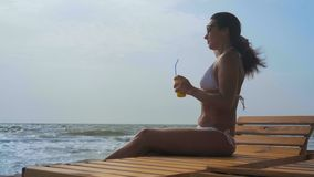 Beautiful woman in the white swimsuit c cocktail in hand sits on a wooden deck chair and corrects her hair on the sea. Beautiful woman in the white swimsuit and stock video