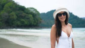 Beautiful woman in a white swimsuit and hat walking on the beach.Travel and vacation concept.  stock footage