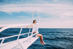 Beautiful woman in white swimsuit standing on the nose of the yacht and spreading hands apart at a sunny summer day, breeze develo Stock Photo