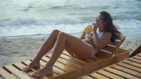 A beautiful woman in a white swimsuit and sun glasses lies on a wooden deck chair on the sea beach and drinks a cocktail. Beautiful woman in the white swimsuit stock video