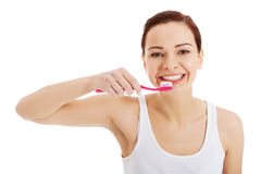 Beautiful woman in white top is brushing her teeth. Stock Photos