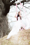 Beautiful woman in white wedding dress shaking on a swing Royalty Free Stock Photography