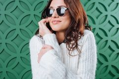 Beautiful woman in white winter sweater and black sunglasses talking by smartphone. On green Royalty Free Stock Photo
