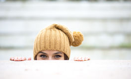 Beautiful woman who is hiding and looks like she is playing Royalty Free Stock Images