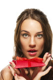 Beautiful woman with wide open eyes holding red pr Stock Photos