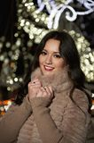 Beautiful woman with winter city lights behind Royalty Free Stock Photo