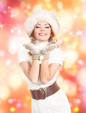 A beautiful woman in winter clothes on a bright background Royalty Free Stock Images