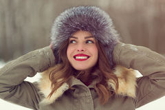 Beautiful woman in winter coat and fur hat. At winter forest Stock Image