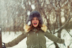 Beautiful woman in winter coat and fur hat. In the winter forest Royalty Free Stock Images