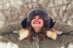 Beautiful woman in winter coat and fur hat. In the winter forest Royalty Free Stock Photo