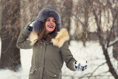 Beautiful woman in winter coat and fur hat. In the winter forest Royalty Free Stock Image