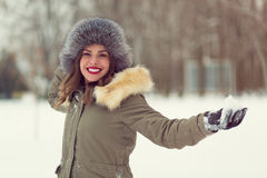 Beautiful woman in winter coat and fur hat. In the winter forest Royalty Free Stock Photos