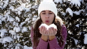 Beautiful woman in winter hat blows off snow from hands stock video footage
