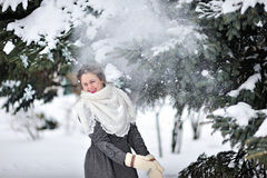 Beautiful woman in winter knitted mittens throws snow Royalty Free Stock Image