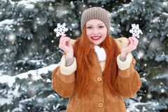 Beautiful woman on winter outdoor posing with big snowflake toys, holiday concept, snowy fir trees in forest, long red hair, weari Stock Photo