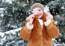 Beautiful woman on winter outdoor posing with big snowflake toys, holiday concept, snowy fir trees in forest, long red hair, weari Royalty Free Stock Images
