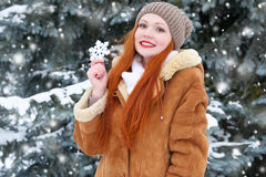 Beautiful woman on winter outdoor posing with big snowflake toys, holiday concept, snowy fir trees in forest, long red hair, weari Royalty Free Stock Photography