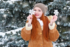Beautiful woman on winter outdoor posing with big snowflake toys, holiday concept, snowy fir trees in forest, long red hair, weari Stock Photos