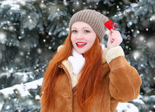 Beautiful woman on winter outdoor posing with heart shape toys, holiday concept, snowy fir trees in forest, long red hair, wearing Stock Image