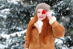 Beautiful woman on winter outdoor posing with heart shape toys, holiday concept, snowy fir trees in forest, long red hair, wearing Royalty Free Stock Photos