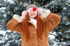 Beautiful woman on winter outdoor posing with heart shape toys, holiday concept, snowy fir trees in forest, long red hair, wearing Royalty Free Stock Images