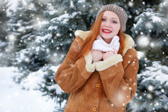 Beautiful woman on winter outdoor, snowy fir trees in forest, long red hair, wearing a sheepskin coat Royalty Free Stock Image