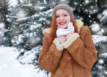 Beautiful woman on winter outdoor, snowy fir trees in forest, long red hair, wearing a sheepskin coat Stock Photography