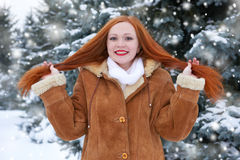 Beautiful woman on winter outdoor, snowy fir trees in forest, long red hair, wearing a sheepskin coat Stock Photos