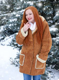 Beautiful woman on winter outdoor, snowy fir trees in forest, long red hair, wearing a sheepskin coat Royalty Free Stock Images