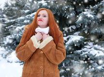 Beautiful woman on winter outdoor, snowy fir trees in forest, long red hair, wearing a sheepskin coat Stock Image