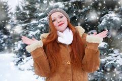 Beautiful woman on winter outdoor, snowy fir trees in forest, long red hair, wearing a sheepskin coat Stock Images