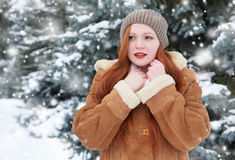 Beautiful woman on winter outdoor, snowy fir trees in forest, long red hair, wearing a sheepskin coat Royalty Free Stock Photos