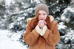 Beautiful woman on winter outdoor, snowy fir trees in forest, long red hair, wearing a sheepskin coat Royalty Free Stock Photography