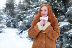 Beautiful woman on winter outdoor, snowy fir trees in forest, long red hair, wearing a sheepskin coat Stock Photo